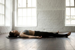 Young attractive woman in Savasana pose, white loft studio backg Royalty Free Stock Photos