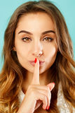 Young attractive woman saying shh gesture over blue background. Stock Photos