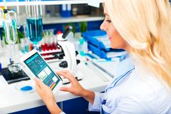 Young attractive woman scientist using tablet computer in the la Stock Photo