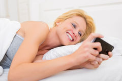 Young attractive woman sending ttext in a bed Stock Photography