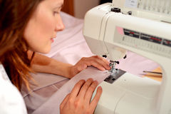 Young attractive woman sewing on machine