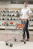Young attractive woman with shopping cart Stock Photography