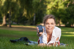 Young, attractive woman shows her smartphone Royalty Free Stock Images