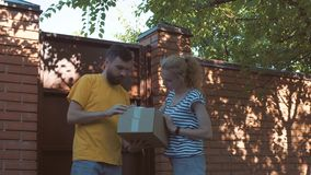 The postman delivers a parcel for a young woman stock video