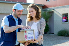 Young attractive woman signing on delivery paper Royalty Free Stock Image