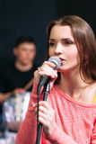 Young attractive woman singing karaoke in bar Stock Photo