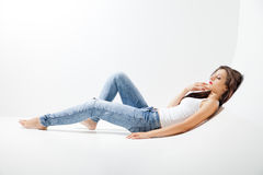 Young attractive woman siting on the studio floor Stock Photos