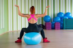 Young attractive woman sits a back on the ball in fitness in the Royalty Free Stock Photography