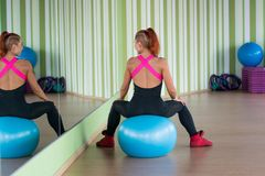 Young attractive woman sits a back on the ball in fitness near a Stock Photos
