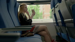 Young attractive woman sits in train car. Girl drinking coffee in train stock video