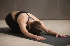 Young attractive woman sitting in Balasana pose, grey studio bac Stock Images