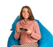 Young attractive woman sitting on blue beanbag chair and playing. Young attractive woman sitting on blue beanbag chair for living room or other room and playing Stock Photography