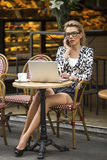 Young attractive  woman sitting c laptop at an outdoor cafe and talking on a cell phone. Royalty Free Stock Photo