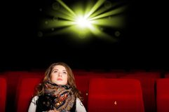Young attractive woman sitting in a cinema Royalty Free Stock Photo