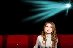 Young attractive woman sitting in a cinema Royalty Free Stock Images