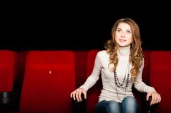 Young attractive woman sitting in a cinema Stock Images