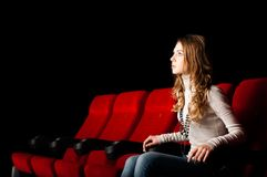 Young attractive woman sitting in a cinema Royalty Free Stock Photography