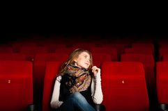 Young attractive woman sitting in a cinema Royalty Free Stock Image