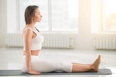 Young attractive woman sitting in Dandasana pose, white color ba Stock Photo