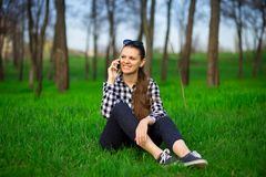 Young attractive woman sitting on grass and talk by phone relaxing resting. In sunny weather in field on bright green background. Lifestyle, leisure concept Stock Images