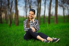 Young attractive woman sitting on grass and talk by phone. Relaxing resting in sunny weather in field on bright green background. Lifestyle, leisure concept Stock Images