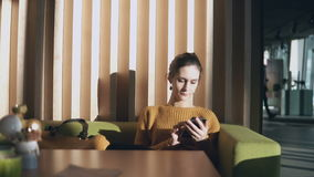 Young attractive woman sitting in the hotel and holding smartphone. Businesswoman surf the Internet on sofa in hall. Female working in bright sunny morning stock footage