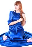 Young attractive woman sitting in a long blue evening dress Royalty Free Stock Photography