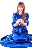 Young attractive woman sitting in a long blue evening dress Royalty Free Stock Images