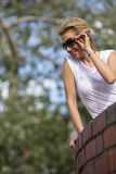 Young attractive woman sitting and looking down from brick fence in the Park. Royalty Free Stock Photo