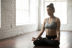 Young attractive woman sitting in Lotus pose, white loft studio Stock Photo