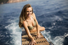 Young attractive woman sitting on  luxury yacht floating at sea Royalty Free Stock Image
