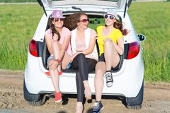 Young attractive woman sitting in the open trunk Royalty Free Stock Photos