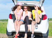Young attractive woman sitting in the open trunk Stock Photo