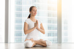 Young attractive woman sitting in Padmasana pose against floor w Stock Image