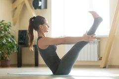Young attractive woman sitting in Paripurna Navasana pose, home Stock Photos