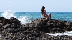 Young attractive woman sitting on the rocks stock video