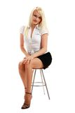 A young attractive woman sitting on stool Stock Photography