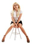 A young attractive woman sitting on stool Stock Image