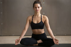 Young attractive woman sitting in Sukhasana pose, grey studio ba Royalty Free Stock Photography