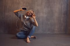 Young and attractive woman with smartphone and large headphones, sitting on the floor. Music in the mobile app. Young and attractive woman with a smartphone and stock photo