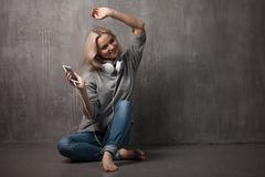 Young and attractive woman with smartphone and large headphones, sitting on the floor. Music in the mobile app. Young and attractive woman with a smartphone and stock photography