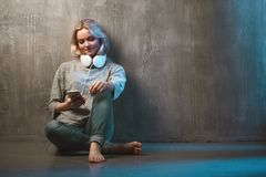 Young and attractive woman with smartphone and large headphones, sitting on the floor. Music in the mobile app. Young and attractive woman with a smartphone and royalty free stock photography
