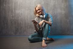 Young and attractive woman with smartphone and large headphones, sitting on the floor. Music in the mobile app. Young and attractive woman with a smartphone and royalty free stock photos