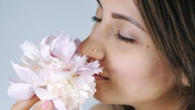 Young woman sniffing pink flower stock video footage