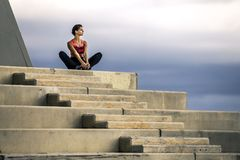 Young and attractive woman in sportswear is sitting in meditation pose on the stairs. Young and attractive woman in sportswear is sitting in meditation pose on Stock Images