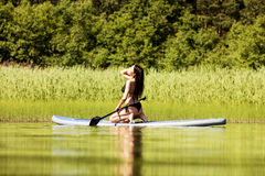 Young attractive woman on stand up paddle board.  Stock Photo