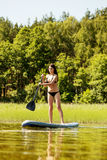 Young attractive woman on stand up paddle board.  Stock Photos