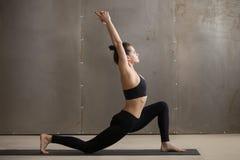 Young attractive woman standing in anjaneyasana pose, grey studi. Young attractive yogi woman practicing yoga, standing in anjaneyasana exercise, Horse rider stock image