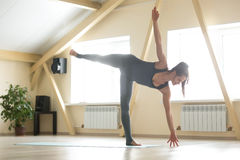 Young attractive woman standing in Ardha Chandrasana pose, home Stock Photo