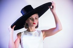 Young attractive woman standing on the background of a white wall in big hat. Holding on her hat royalty free stock image